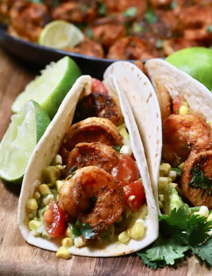 Shrimp tacos on a cutting board with lime halves.