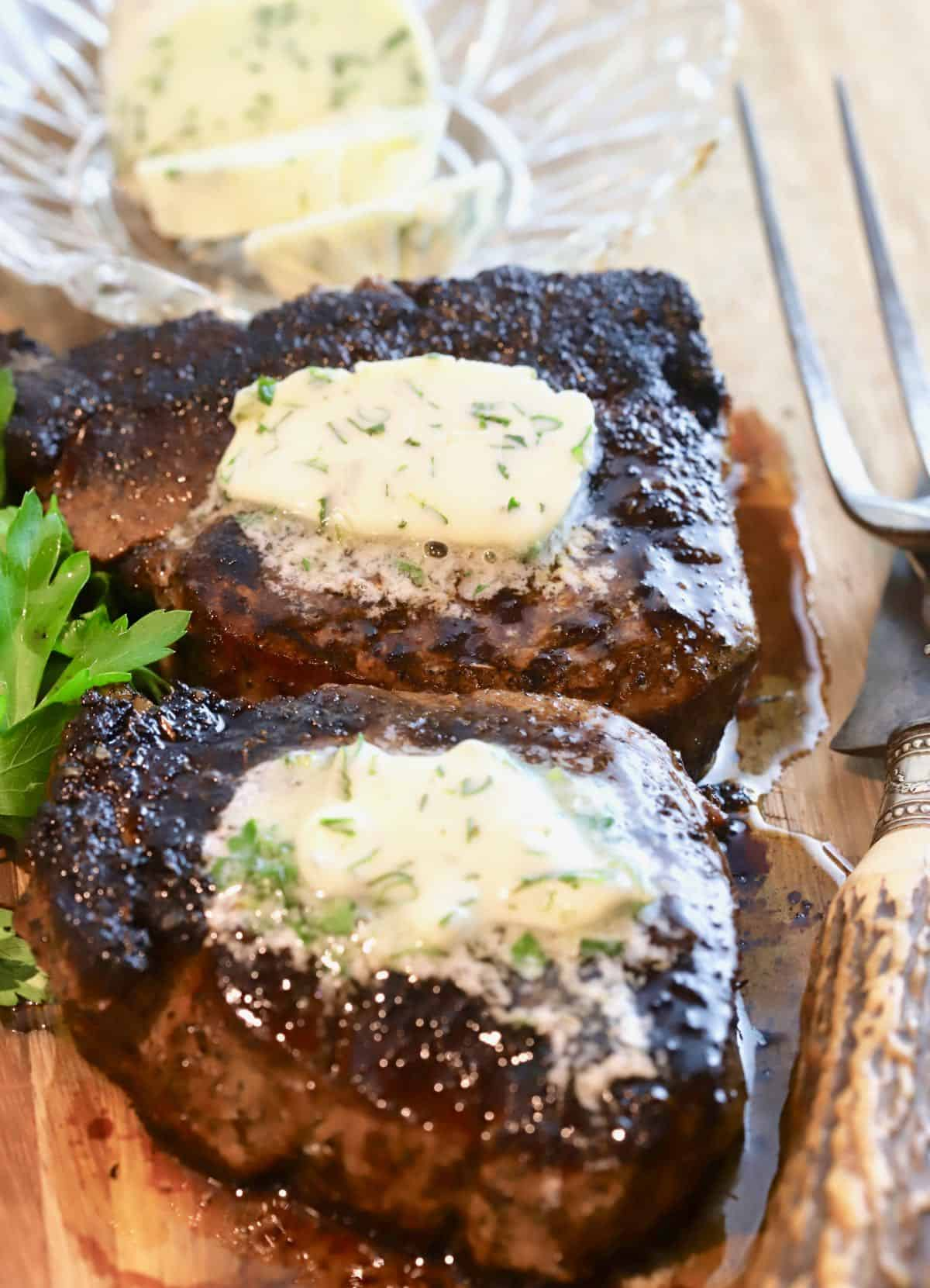 Two blackened steaks topped with garlic herb butter.