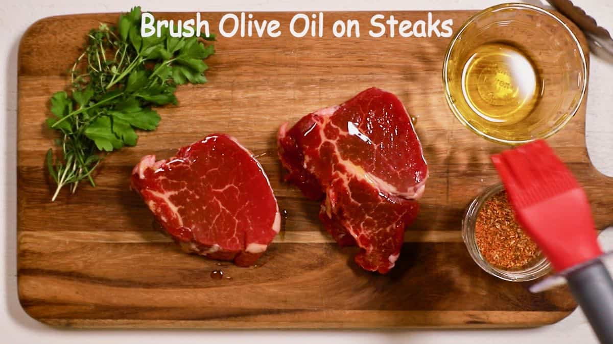Brushing olive oil on filet mignons.