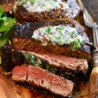 Two blackened steaks on a wooden cutting board.