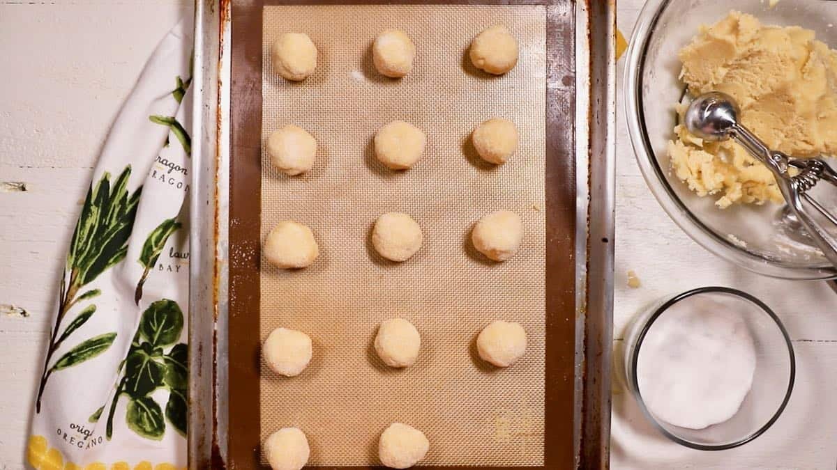 Balls of shortbread dough on a baking sheet.