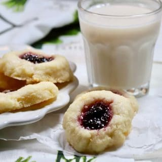 A glass of milk and blueberry thumbprint cookies on a plate.