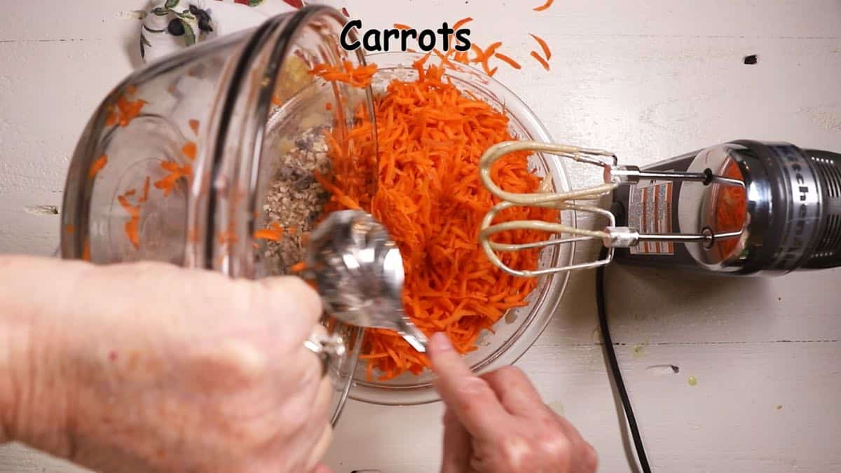 Adding shredded carrots to cake batter.