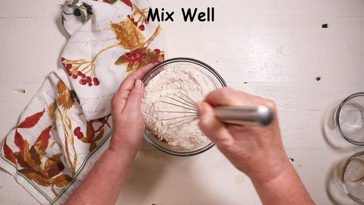 Mixing flour, baking soda and cinnamon in a bowl with a whisk.