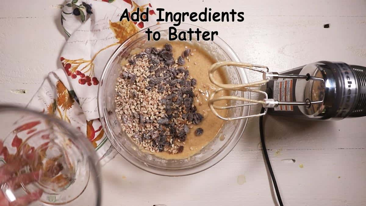 Adding raisins and pecans to cake batter.