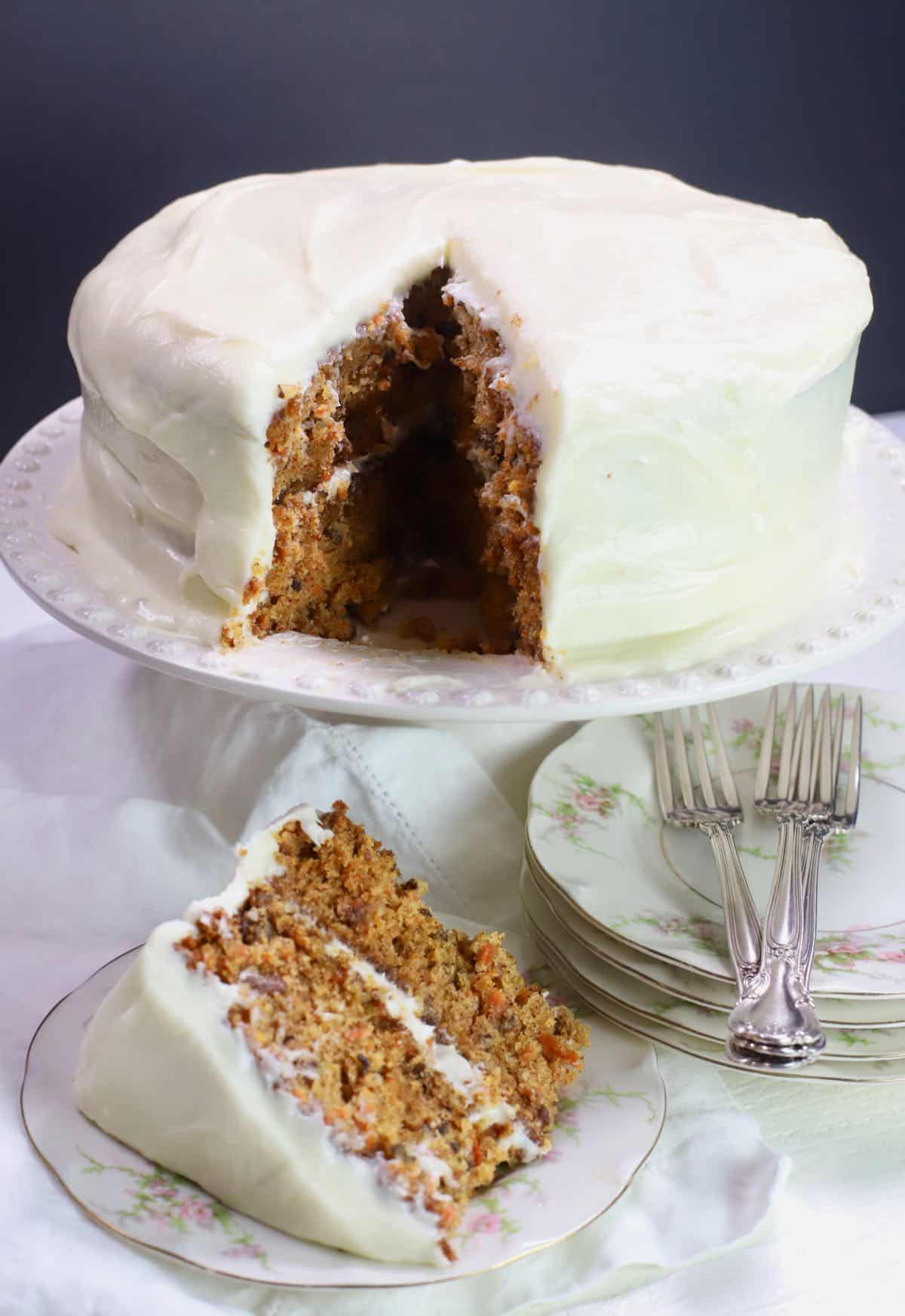 Carrot cake on a cake platter with a slice cut.