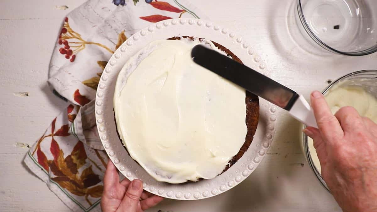 Icing the first layer of a cake on a white cake platter.