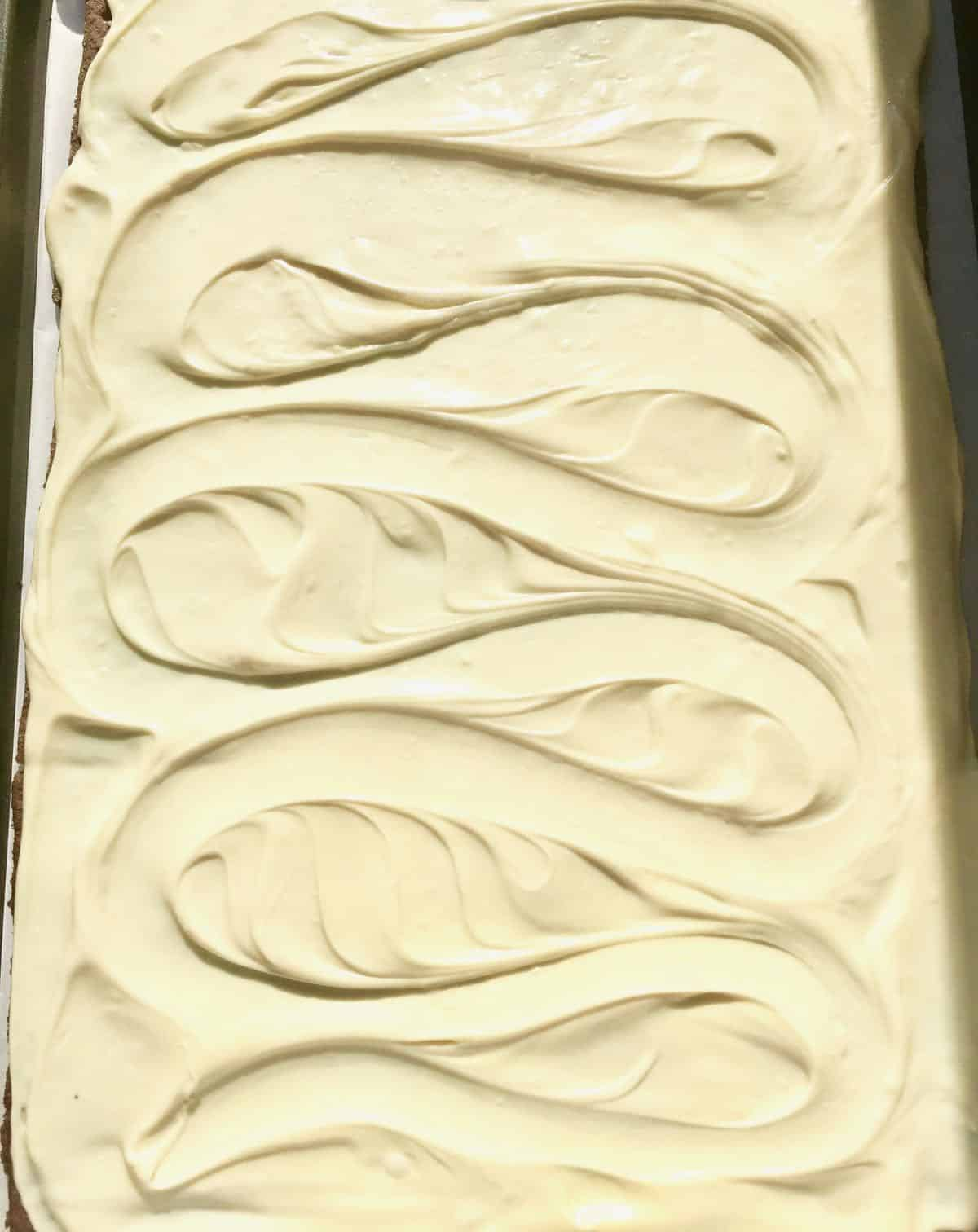 Melted white chocolate spread over graham crackers on a baking sheet.
