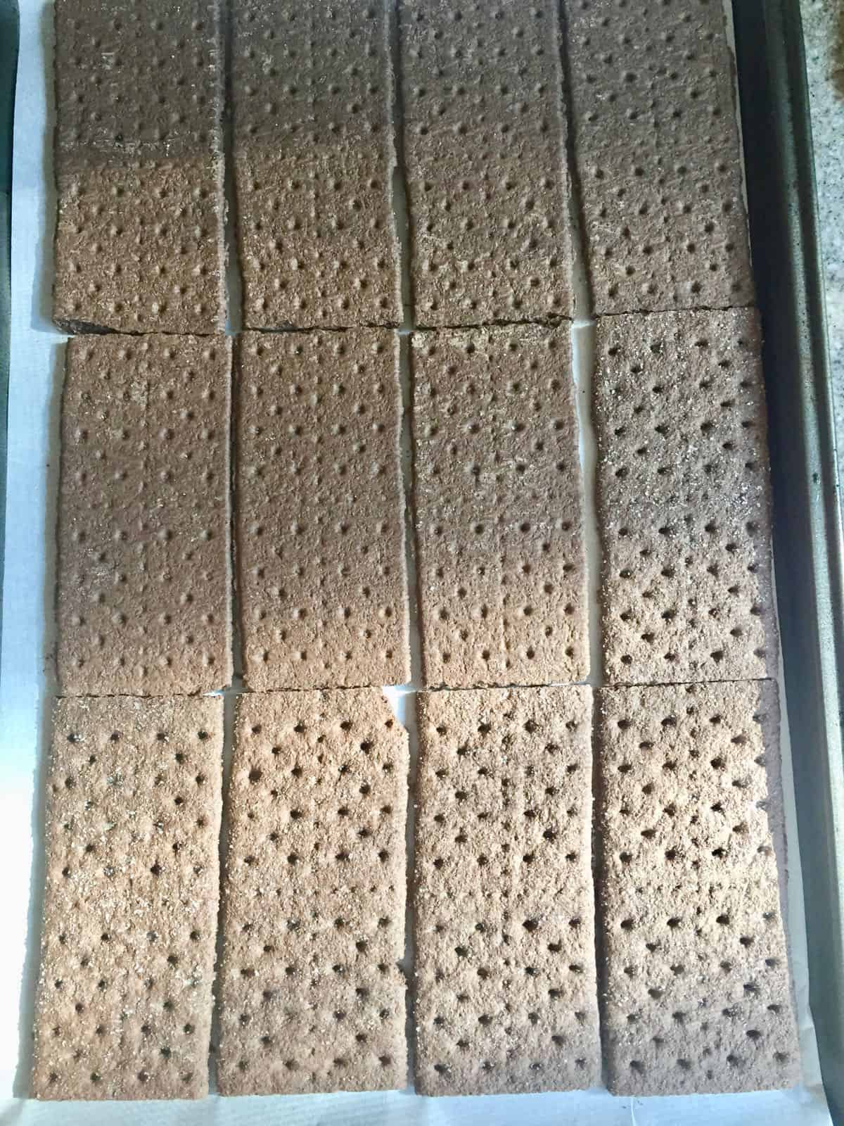 Chocolate graham crackers on a baking sheet.
