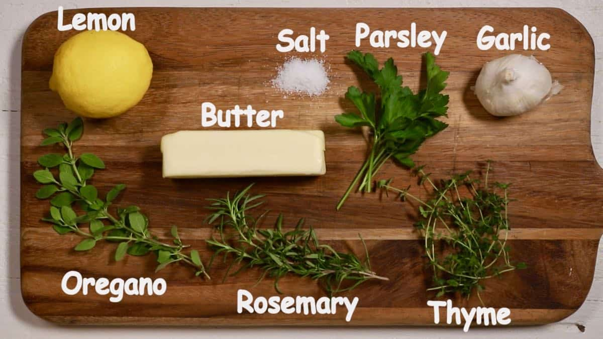 Ingredients for garlic herb butter on a cutting board.