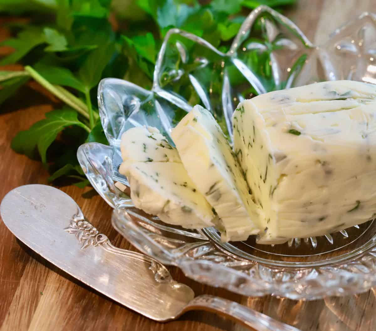 A cut glass dish with garlic herb butter slices.