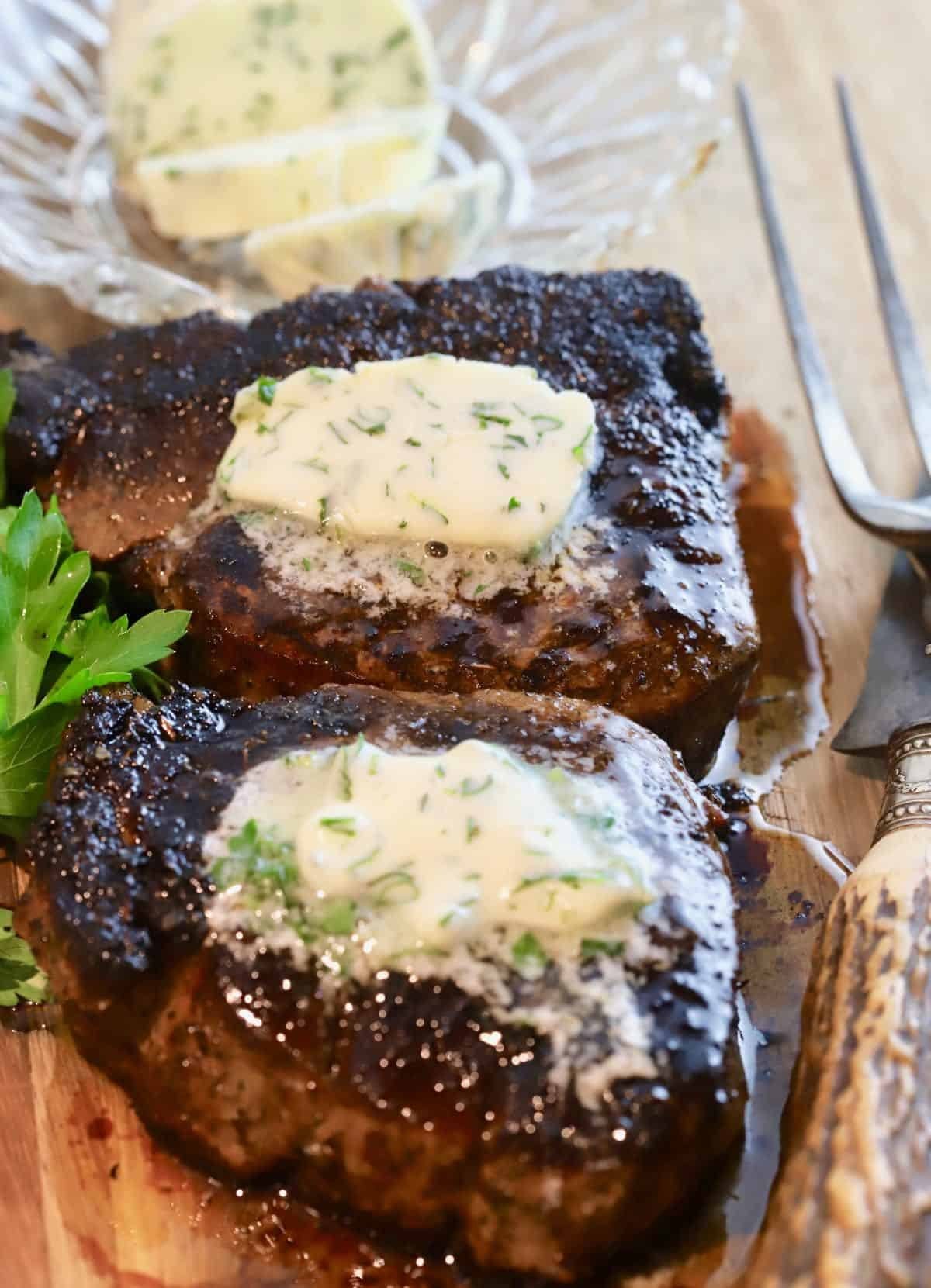 Two steaks topped with pats of garlic herb butter.