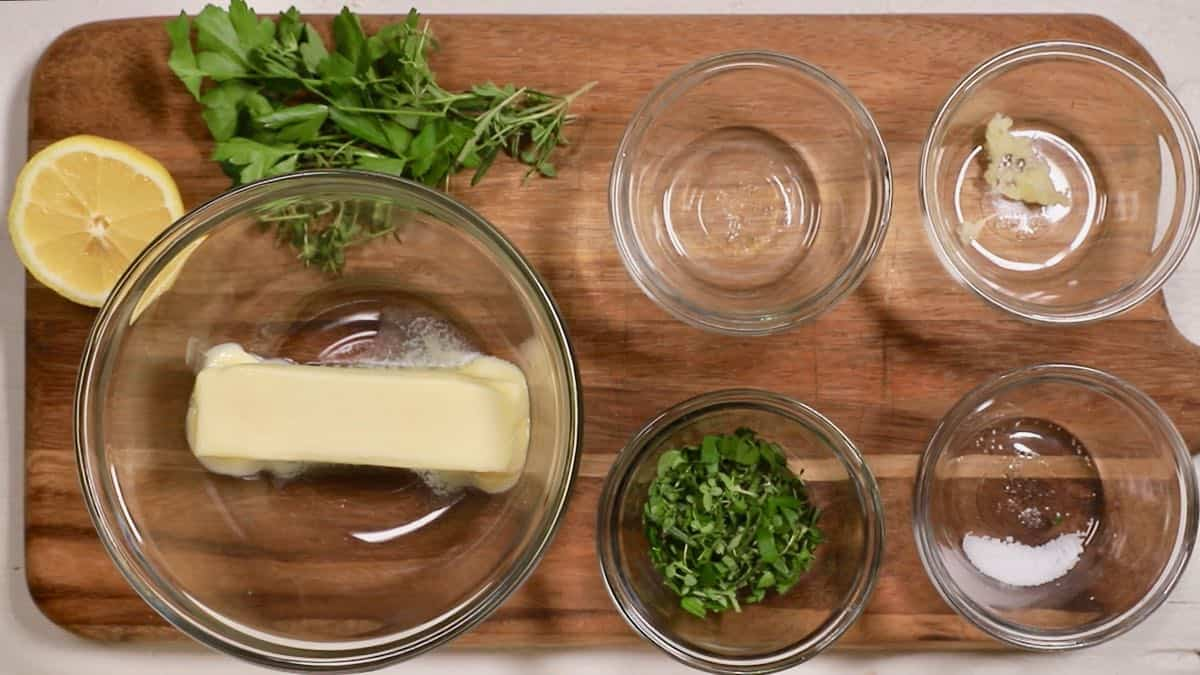Butter in a clear glass bowl and small bowls of herbs, lemon, juice and garlic.
