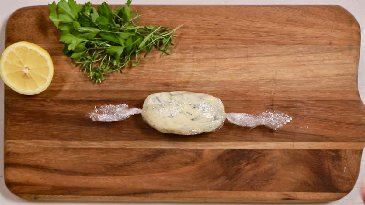 A roll of garlic herb butter in plastic wrap ready to refrigerate.