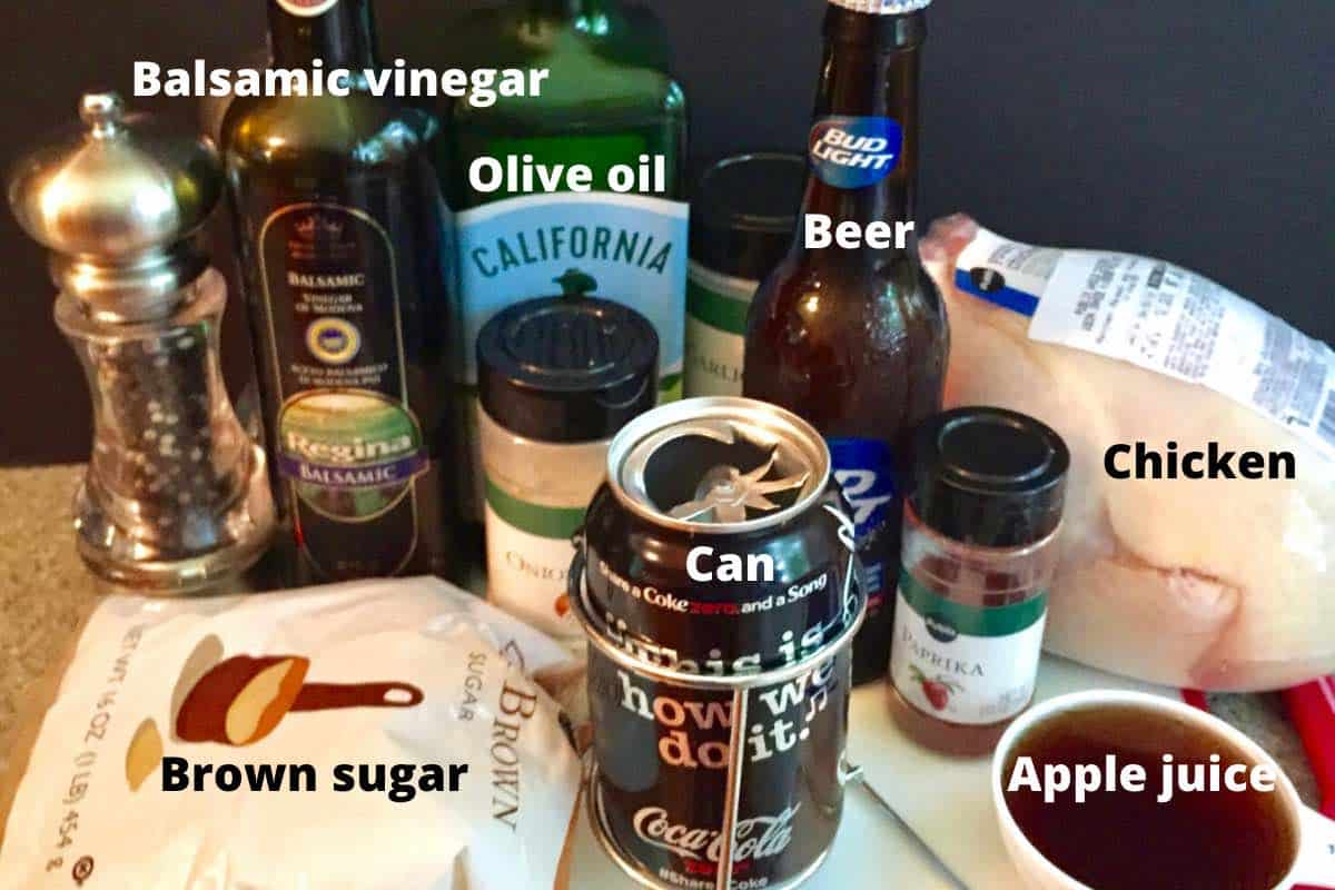 A soda can, a beer, olive oil, balsamic vinegar and brown sugar on a kitchen counter.