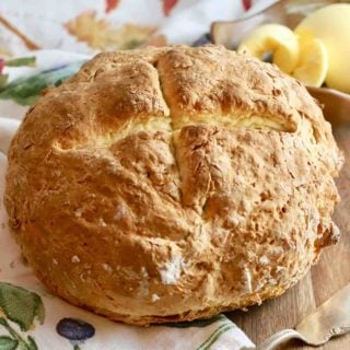 A round of rustic bread on a kitchen towel with a bowl of butter.