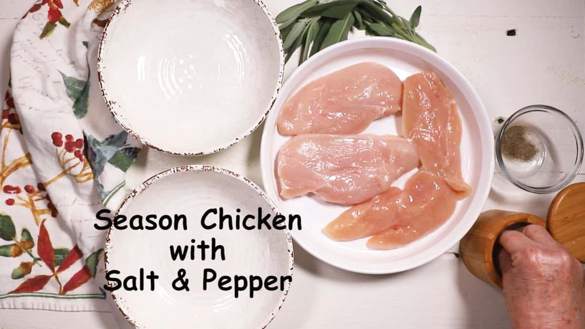Seasoning chicken breasts with salt and pepper.