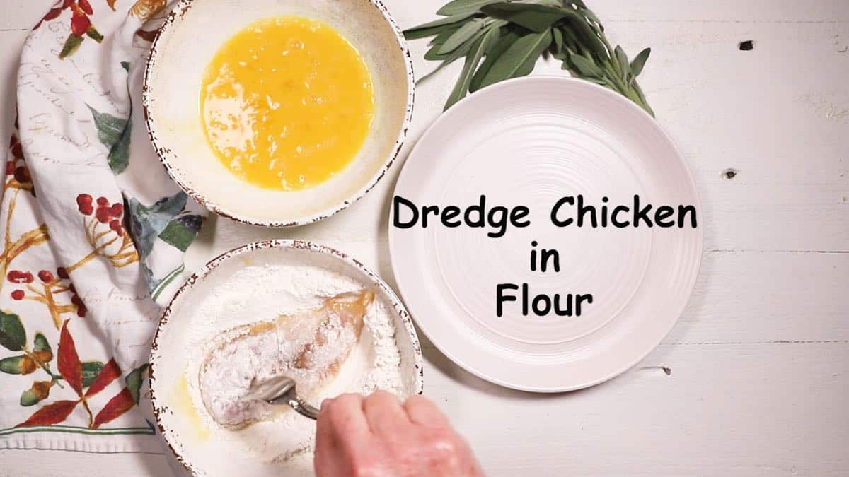 Dredging a chicken breast in flour in a bowl.