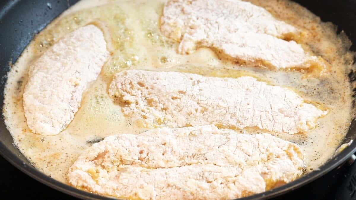 Cooking four chicken breasts in butter in a skillet.