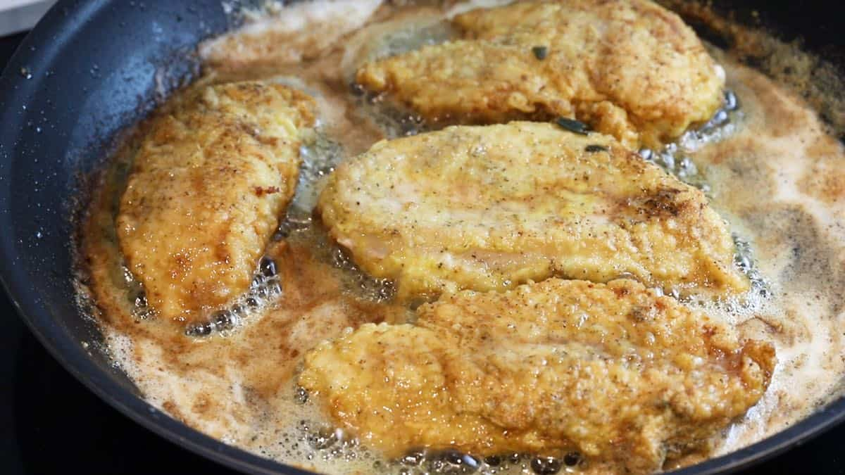Pan frying chicken in butter in a skillet.