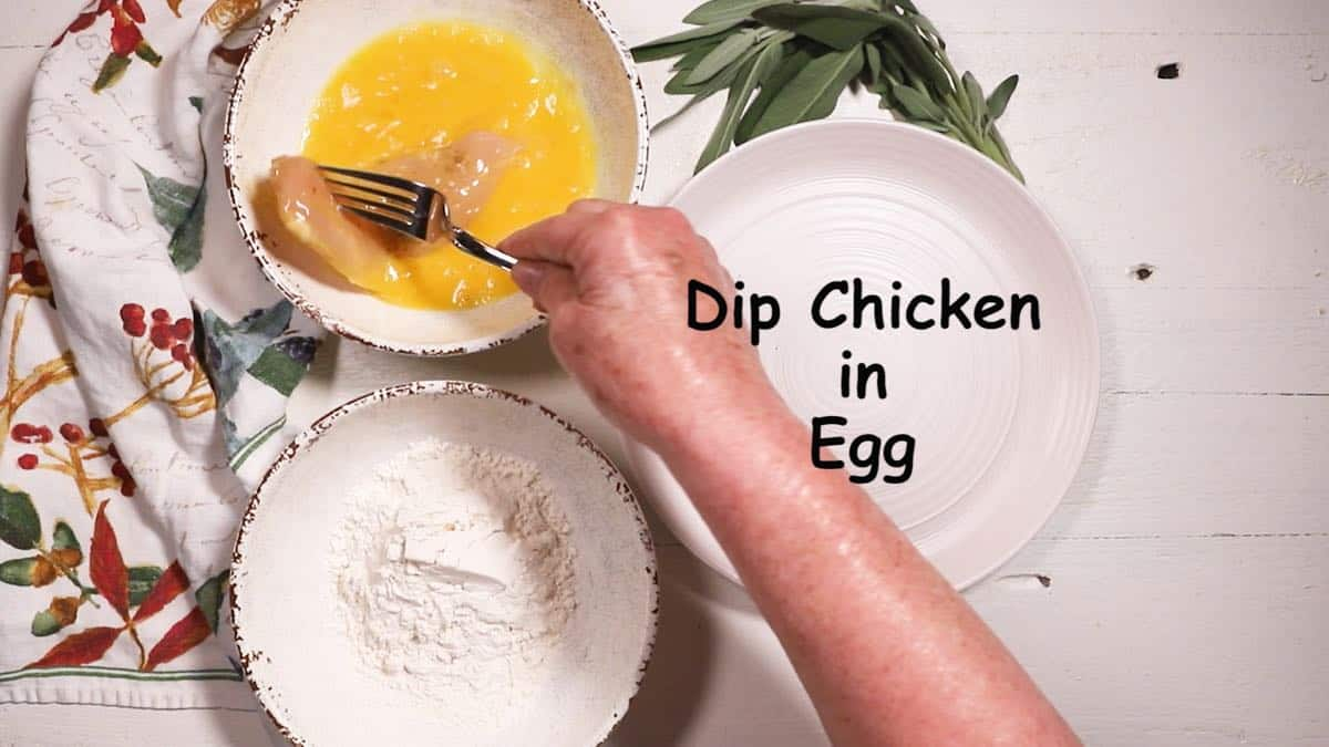 Dipping a piece of chicken into an egg mixture in a white bowl.