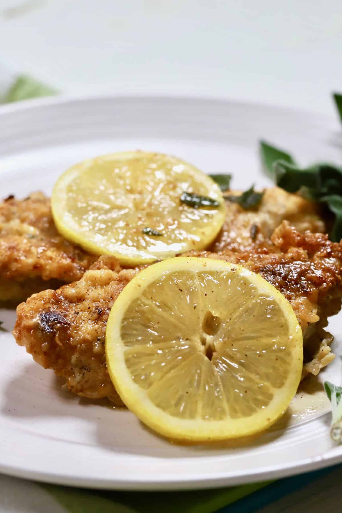 A white plate with slices of lemon on top of two pieces of fried chicken.