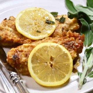 Two pieces of chicken on a white plate garnished with sage and lemon slices.