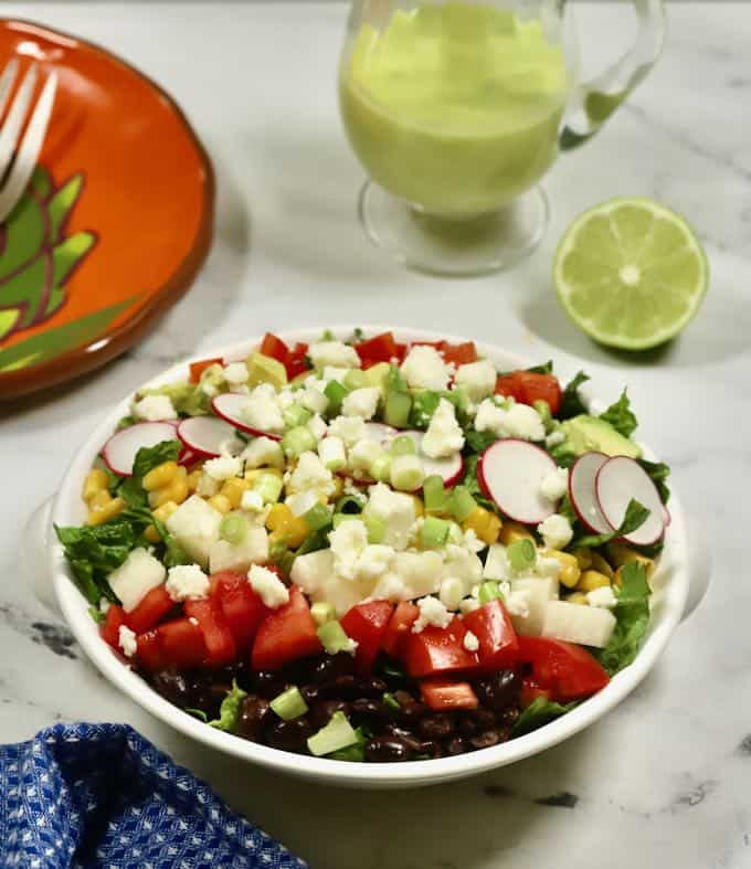 Mexican chopped salad in a white bowl with a small pitcher of honey lime dressing.