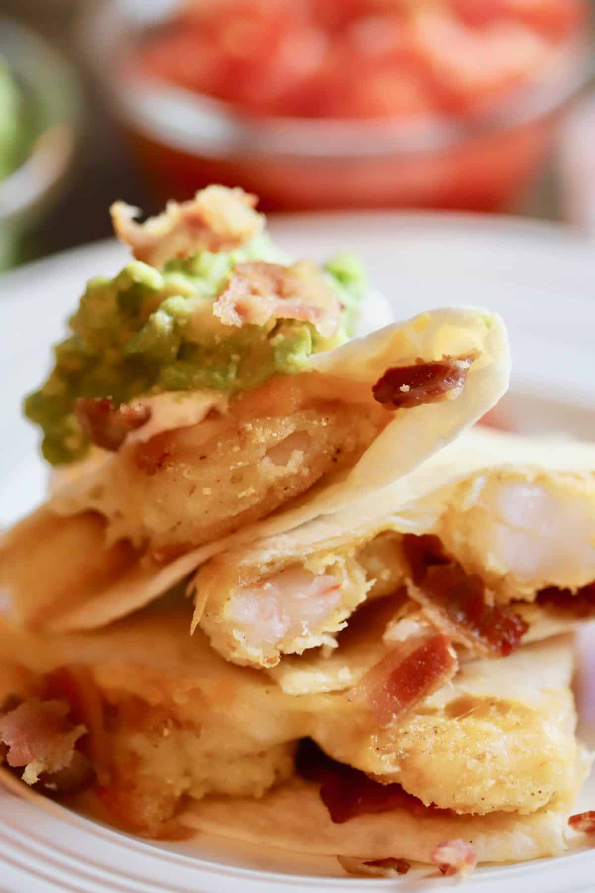Shrimp quesadilla with bacon stacked on top of each other.