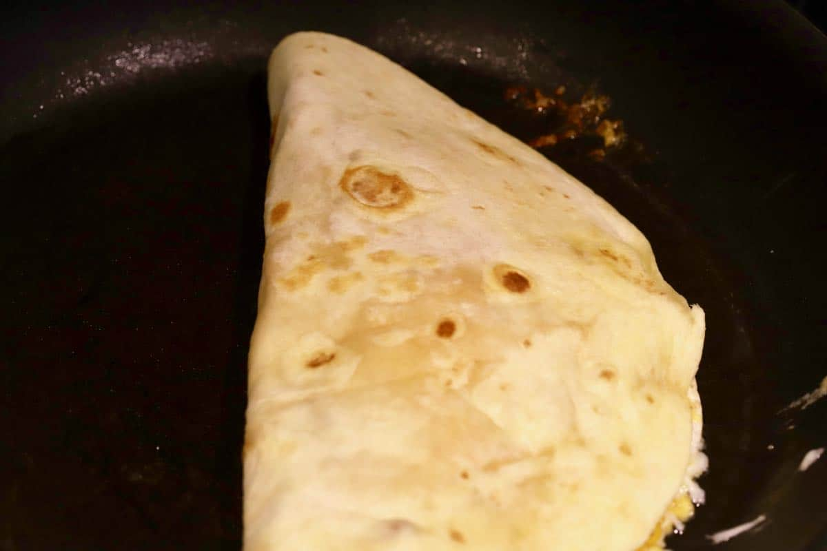 A shrimp quesadilla cooking in a skillet.