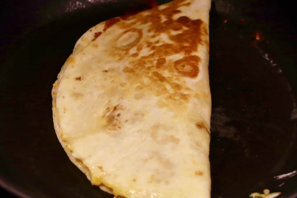 A cooked quesadilla in a black skillat.