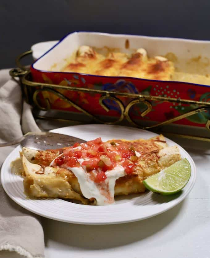A white plate with two enchiladas topped with salsa and sour cream.