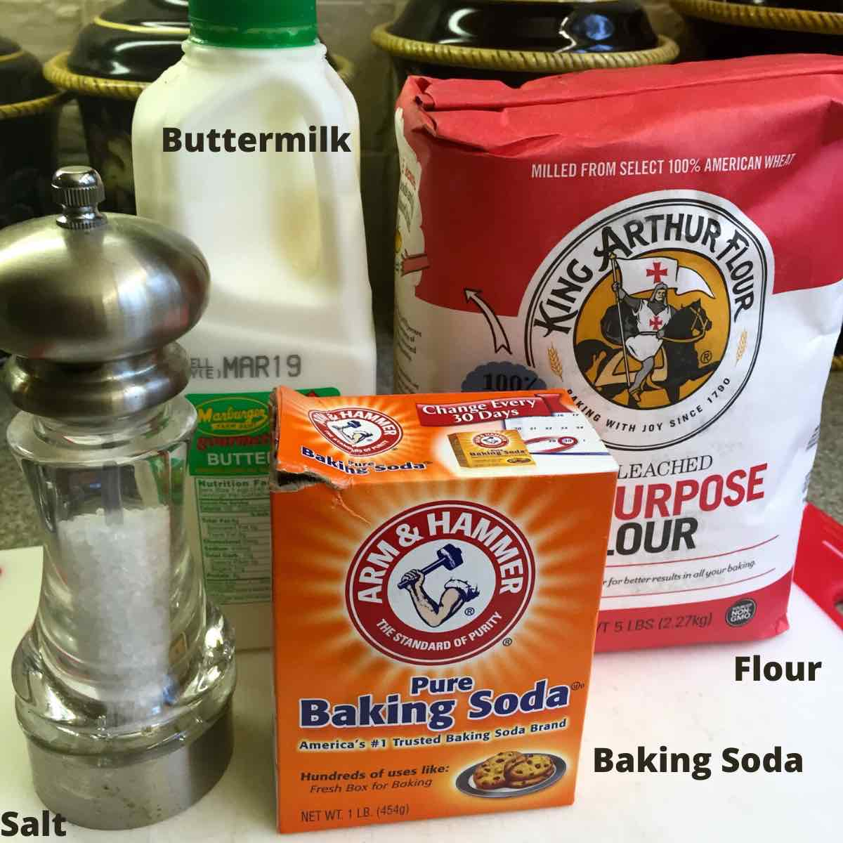 Baking soda, salt, buttermilk and flour on a kitchen counter.
