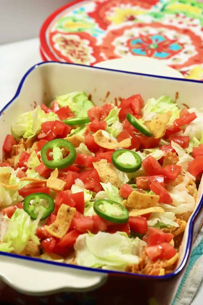 A brightly colored baking dish full of Walking Taco Casserole.