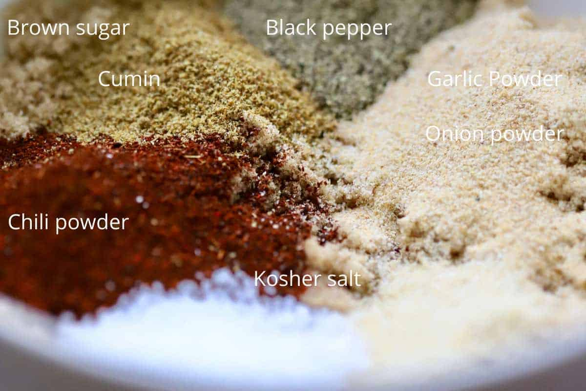 A bowl containing brown sugar, chili powder, cumin, salt, pepper and garlic powder.