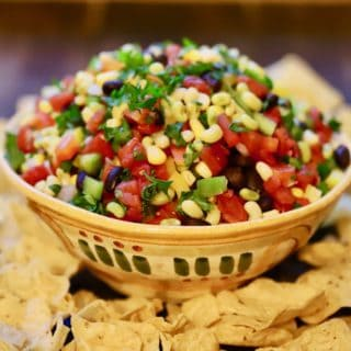 A large southwestern looking bowl full of redneck caviar dip surrounded with tortilla chips.