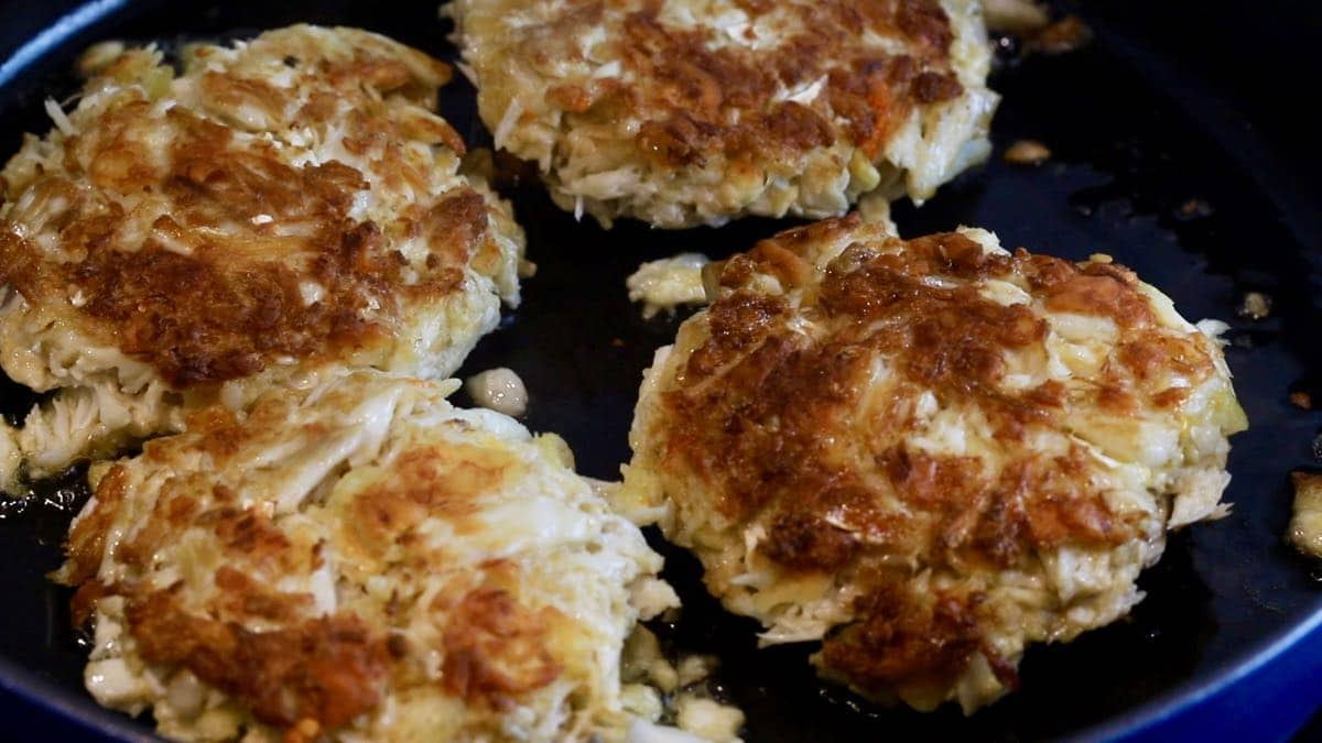 Golden brown crab cakes cooking in a skillet.