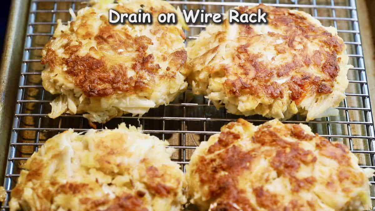 A wire cooling rack with crab cakes just cooked on top.