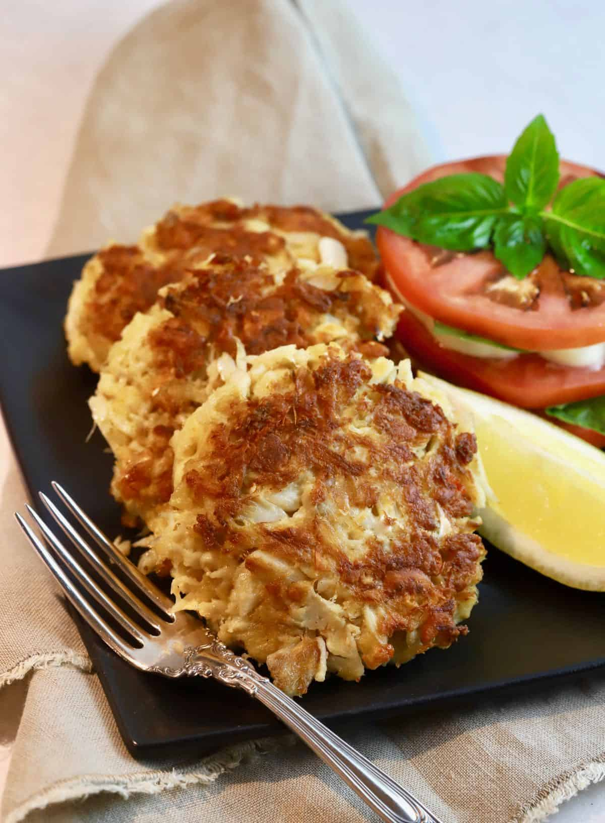 Three crab cakes on a plate with a slice of lemon.