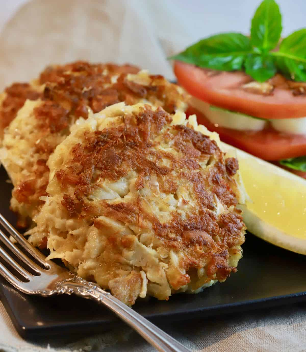 Three crab cakes on a black plate with sliced tomatoes.