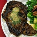 Chili Rubbed Ribeye Steak topped with three pats of Maple Bourbon Butter on a white plate.