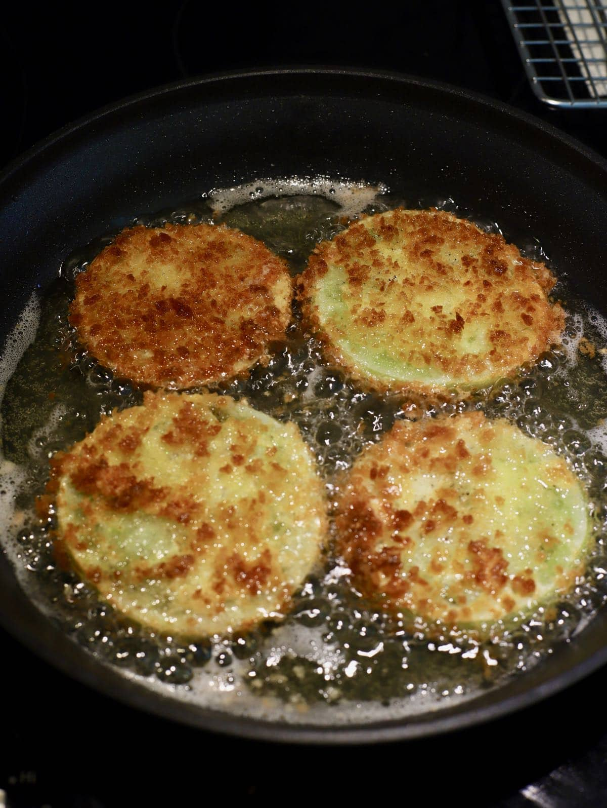 Four tomato slices frying in a large skillet.