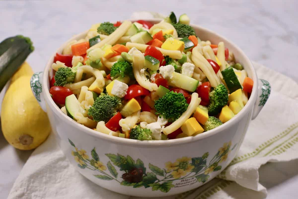 A large bowl with pasta salad topped with broccoli, tomatoes and feta cheese.