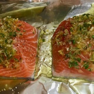 Two salmon fillets topped with herbs on a sheet of aluminum foil.