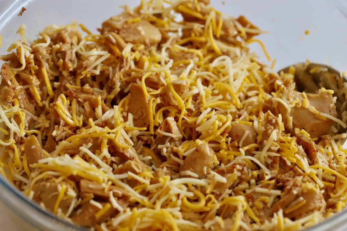Marinated chunks of chicken mixed with shredded cheese.