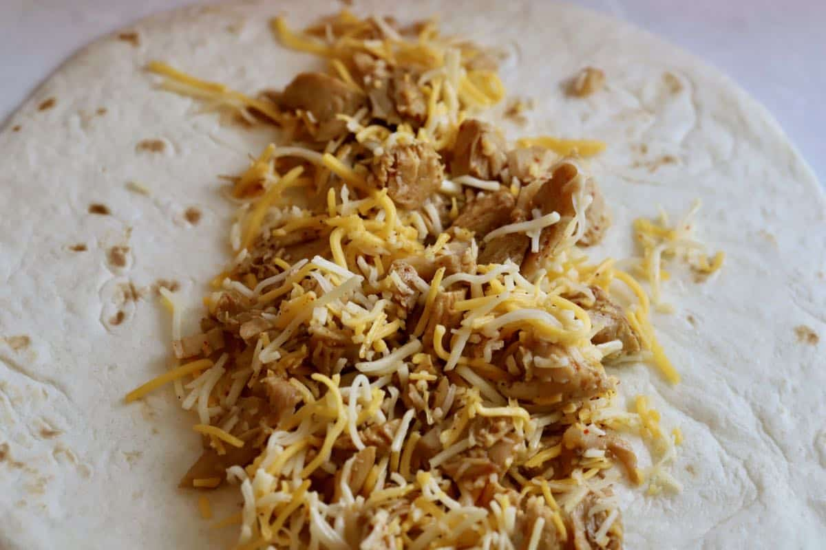 A flour tortilla topped with a mixture of chicken and cheese.