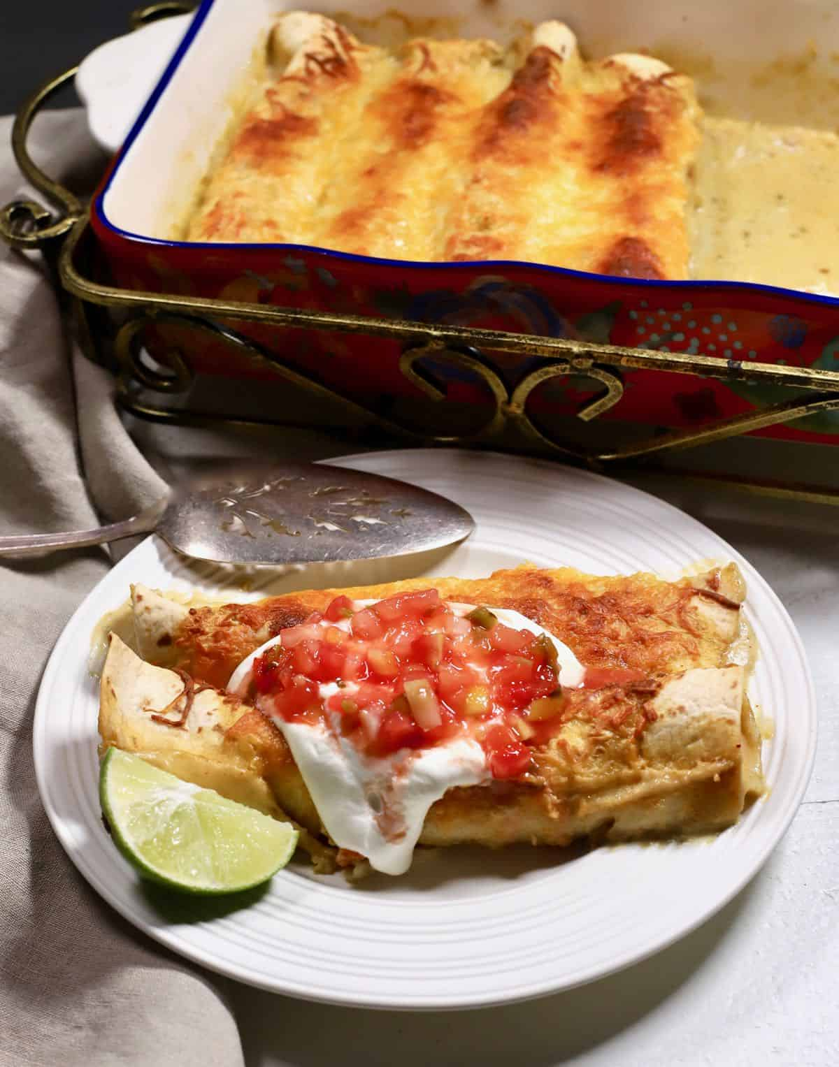 Enchiladas on a plate next to a baking dish full of them.