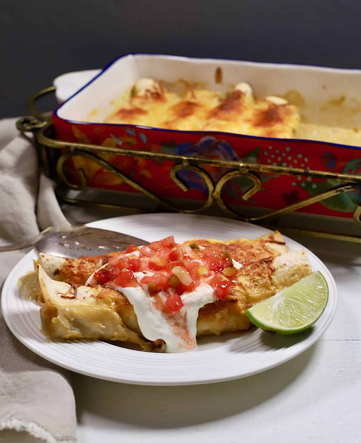Two enchiladas on a plate topped with salsa and sour cream.