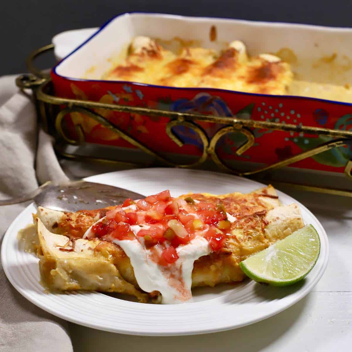 Enchiladas on a plate topped with sour cream and salsa.