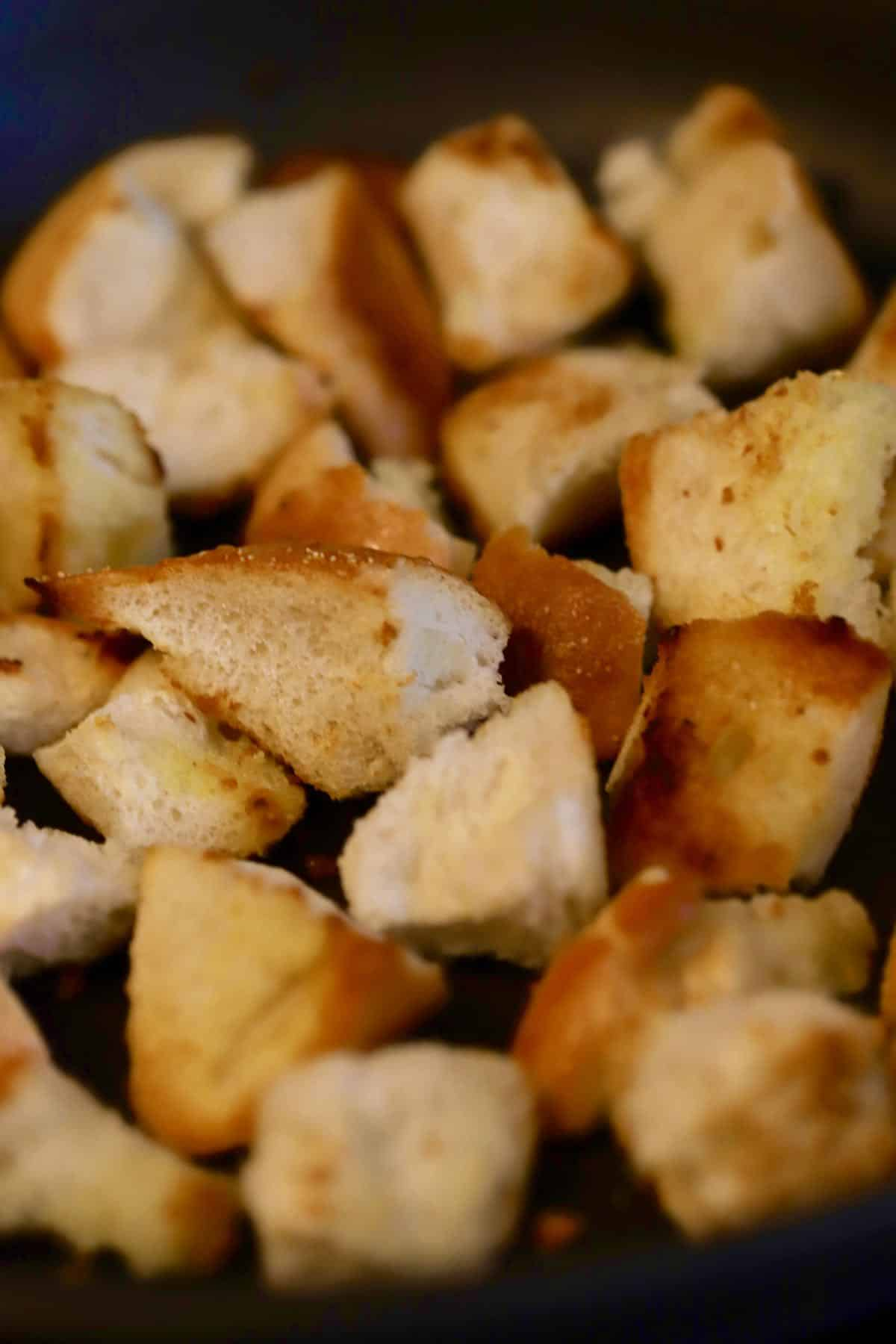 Toasting bread cubes in olive oil in a skillet.